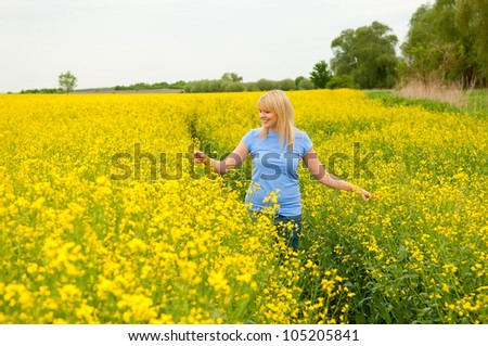 happy young woman in canola field - stock photo