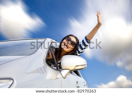 happy young woman in car driving on the road - stock photo
