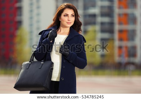 Happy young woman in classic coat with handbag Stylish fashion model outdoor