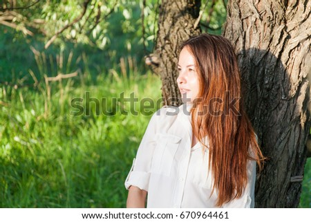 Happy young woman in field. Nature background