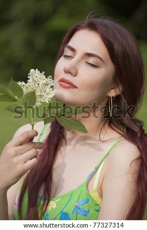 happy young woman in field with flower in her hands - stock photo