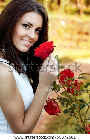 Happy young woman in flower garden smelling red roses - stock photo