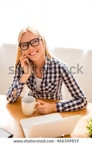 Happy young woman in glasses talk phone and drink tea