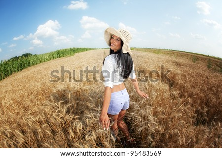 Happy young woman in grain rural field - stock photo