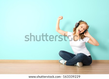 happy young woman in headphones listening to music in a room with a blank wall - stock photo
