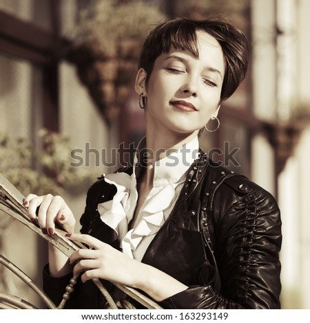 Happy young woman in leather jacket daydreaming - stock photo