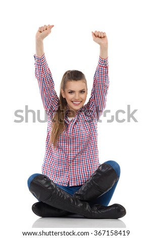 Happy young woman in lumberjack shirt, jeans and boots sitting on a floor with legs crossed and rising arms. Full length studio shot isolated on white. - stock photo