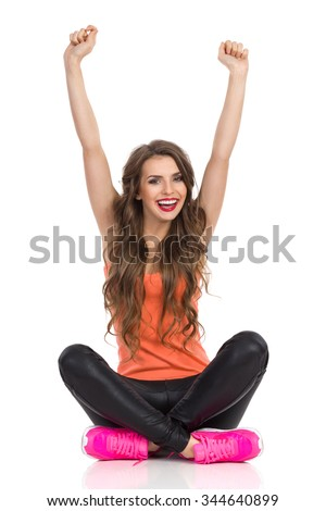 Happy young woman in orange shirt, black leather trousers and pink sneakers sitting on a floor with legs crossed and rising arms. Full length studio shot isolated on white. - stock photo