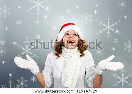 Happy young woman in Santa hat on snowflakes background