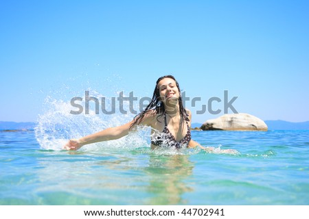 Happy young woman in sea with open hands. - stock photo