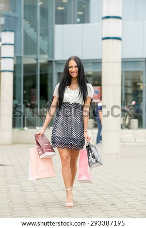 Happy young woman in shopping walking out of shopping mall with bags in their hands. Looking at camera