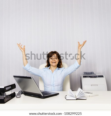 Happy young woman in the office workplace - stock photo