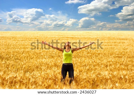 Happy young woman in the yellow field under blue sky