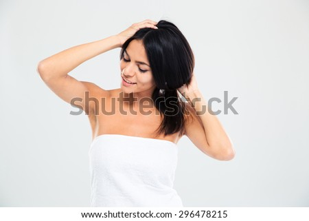 Happy young woman in towel making hairstyle isolated on a white background - stock photo