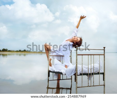 Happy young woman in water on beach. She is enjoying morning nature near retro bed in water, during vacation outdoors.  - stock photo