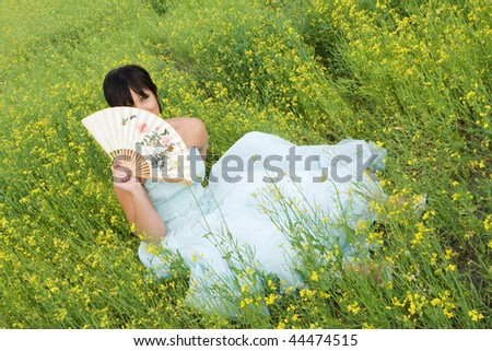 happy young woman in wedding dress on field in summer