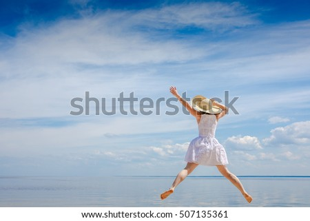 happy young woman in white dress jumping on the beach