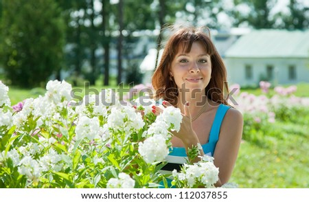 Happy young woman in yard gardening with phlox plant - stock photo