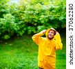 Happy young woman in yellow raincoat under rain - stock photo