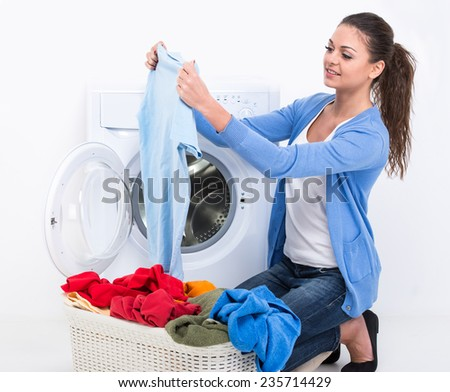 Happy young woman is doing laundry with washing machine at home. - stock photo