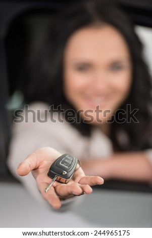 Happy young woman is holding keys to new car and looking at the camera. Focus on keys. - stock photo