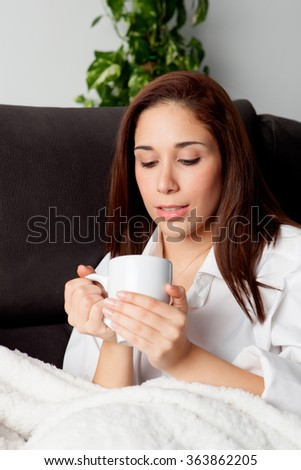 Happy young woman is relaxing on comfortable couch and drinking hot tea - stock photo