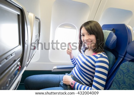 Happy young woman is sitting in the airplane and show thumb up, asian