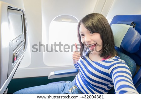 Happy young woman is sitting in the airplane and take a selfie, show thumb up, asian