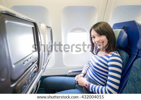 Happy young woman is sitting in the airplane, asian