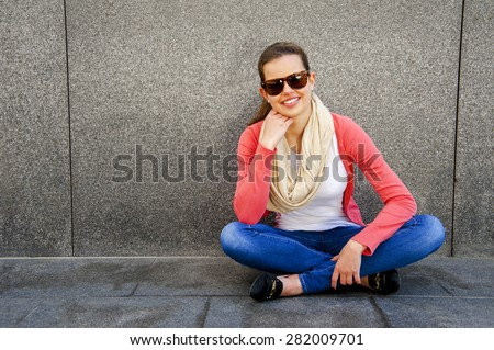 happy young woman is smiling with a blank wall outside with sunglasses - stock photo