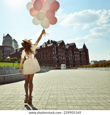 Happy young woman is whirling in park over city background and holding air balloons, toned. - stock photo