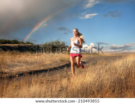 Happy young woman jogging during outdoor workout against sky background with rainbow    - stock photo