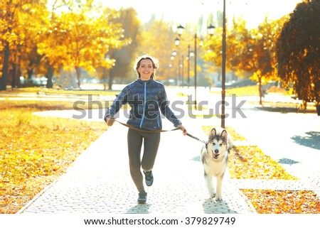 Happy young woman jogging with her dog in park