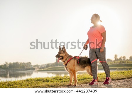 Happy young woman jogging with her German Shepherd Dog - stock photo