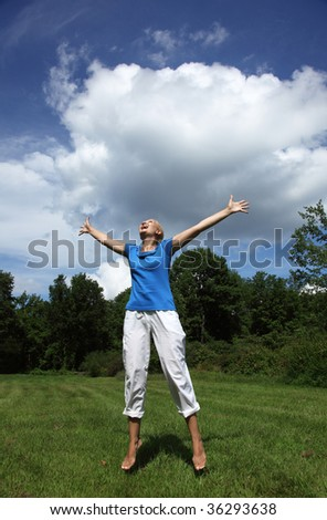 Happy young woman jumping in a green field - stock photo