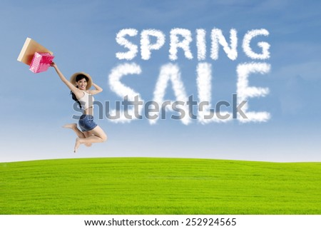 Happy young woman jumping near cloud of spring sale - stock photo