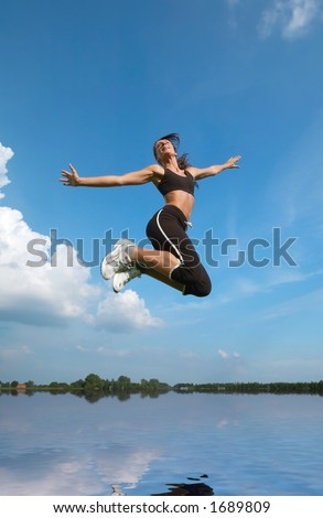 happy young woman  jumping on a sunny day above water - stock photo