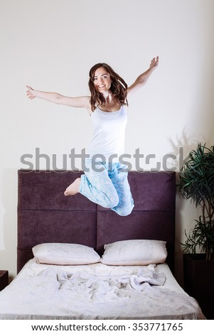 Happy young woman jumping on bed in bedroom