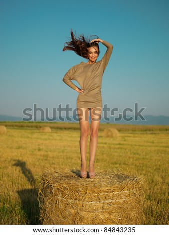 happy young woman jumping on hay stack