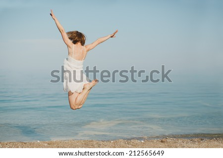 Happy young woman jumping on the beach. Soft lighting  - stock photo