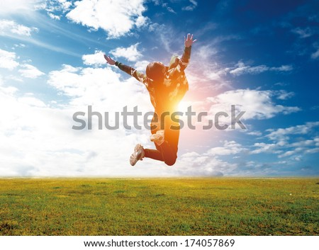 Happy Young Woman Jumping over blue sky. Beauty Girl Having Fun Outdoor. Freedom Concept. Nature. Green Field - stock photo