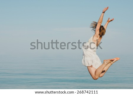 Happy young woman jumping under the water - stock photo