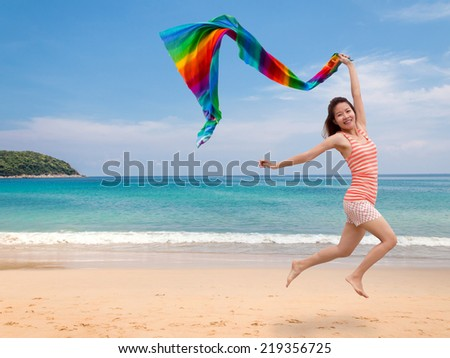 Happy young woman jumping with a colorful scarf on tropical beach - stock photo