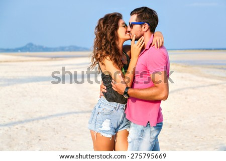 Happy young woman kissing her handsome boyfriend , enjoy their summer vacation on amazing beach, lifestyle portray of stylish hipster couple in love. - stock photo