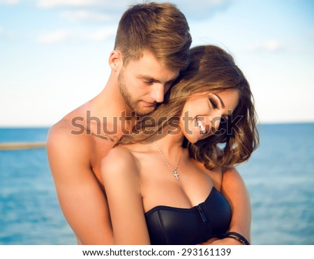 Happy young woman kissing her handsome boyfriend,enjoy their summer vacation on amazing beach,lifestyle portrait of stylish hipster couple in love.positive emotions.holding hands,people in love,smiley - stock photo