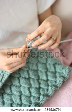 happy young woman knitting on sofa