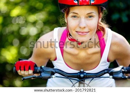 Happy Young woman leaned over the handlebars of her bike. - stock photo