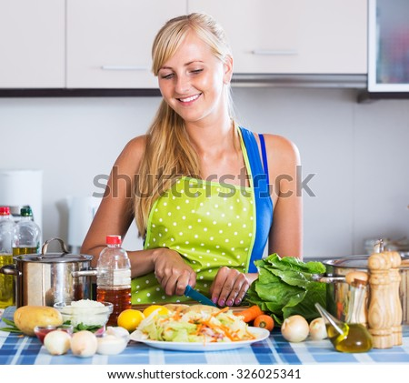 Happy young woman learning new recipe of vegetables at home