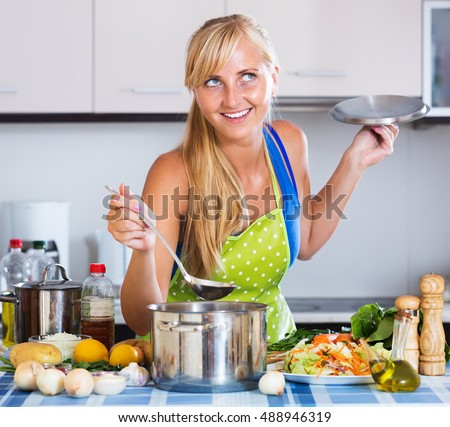 Happy young woman learning new recipe of vegetables in residential kitchen