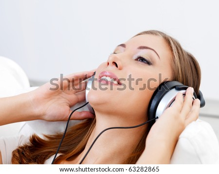 happy young woman listening music in headphone - indoors